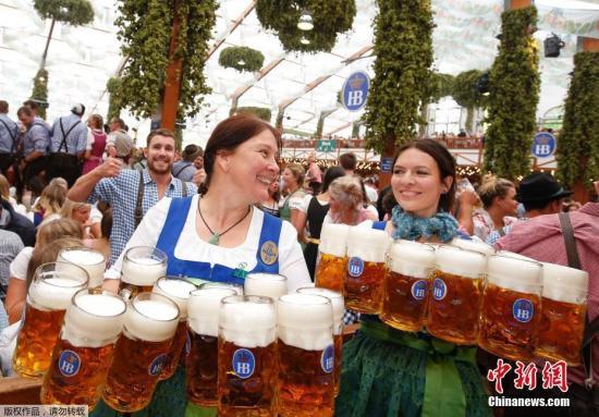 资料图为慕尼黑啤酒节女服务员为食客端啤酒。