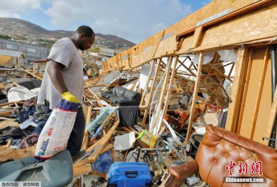 """资料图:近日,美属维尔京群岛遭飓风""""艾尔玛""""过境后,居民返回家中收拾。"""