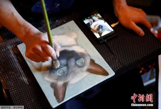 当地时间2017年9月18日,日本东京,当地举办宠物葬礼博览会,一名画家为宠物画像。