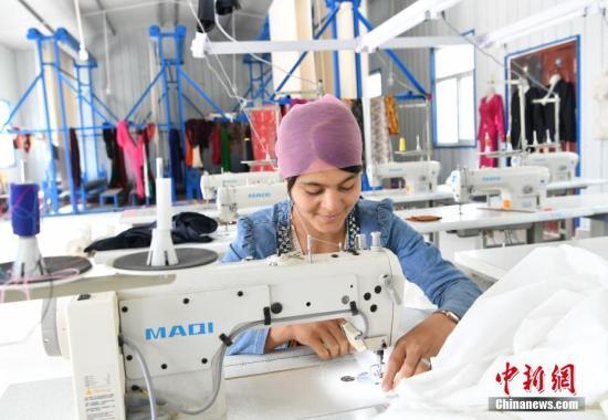 """9月18日,新疆喀什地区麦盖提县库木库萨尔村,一位年轻的维吾尔族姑娘在村里的一间服装合作社内缝制服装。据介绍,在该县各村的""""访汇聚""""驻村工作队的不断努力下,一批服装厂、手套厂、织袜厂等小型加工企业落户乡村,当地很多农村妇女通过技能培训后,走出家门走进工厂,实现当地就业。<a target='_blank' href='http://www.chinanews.com/'>中新社</a>记者 刘新 摄"""