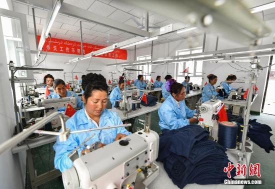 资料图:一间服装加工厂内,当地妇女正在赶制订单。记者 刘新 摄