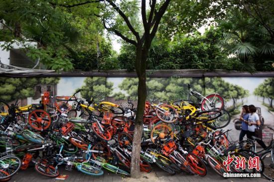 """9月19日,南京碑亭巷内,各种颜色的共享单车堆放在一起,色彩交织的""""叠罗汉""""景象令过往的市民侧目。 <a target='_blank' href='http://www.chinanews.com/'>中新社</a>记者 泱波 摄"""