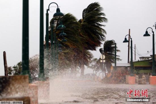 """美国国家飓风研究中心预测,""""玛丽亚""""20日可能抵达美属波多黎各和美属维尔京群岛。波多黎各政府要求居住在木屋或单薄结构房屋的居民疏散至更安全地带。图为波多黎各小镇法哈多的海边,大风将海水吹到公路上。"""