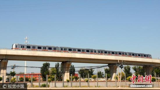 """燕房线是中国内地首条完全自主研发的全自动运行轨道线路。它按照目前世界上列车运行自动化等级的最高级别建设,不仅有条件尝试""""无人驾驶"""",甚至取消了驾驶舱,整个线路的运营、维护都实现了智能化。2016年4月,国家发改委已批准燕房线为国家自主创新示范工程,并将在北京3、12、17、19、新机场线等新一轮北京轨道交通线路建设中推广应用全自动运行模式。燕房线列车最高运行时速80公里,每列4辆编组,定员960人。线路全长16.6公里,共设9座车站,在阎村北站与房山线换乘。杜佳 摄 图片来源:视觉中国"""