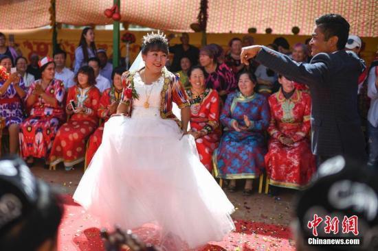 图为新郎与新娘在婚礼现场跳起新疆传统舞蹈。中新社记者 崔楠 摄