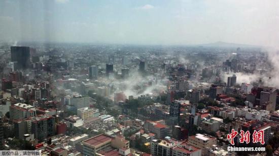 一名市民在墨西哥城地标建筑拉丁美洲塔(Torre Latina)上,用手机拍下了地震后的墨西哥城,建筑倒塌导致城内浓烟四起。