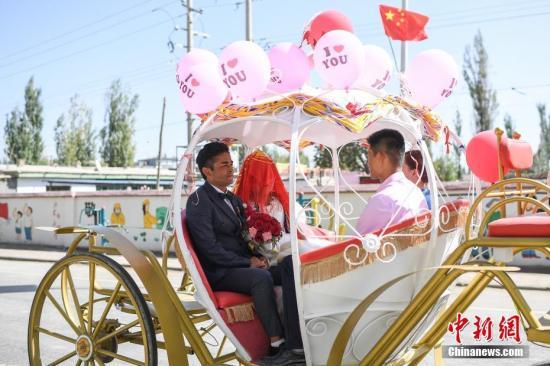 肉先古丽妈妈的维汉家庭再添新成员。图为艾木都拉?孜克拉与新娘历雅馨乘坐婚车前往婚礼现场。中新社记者 崔楠 摄