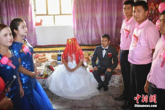 图为新郎新娘在婚房中等待婚礼开始。中新社记者 崔楠 摄