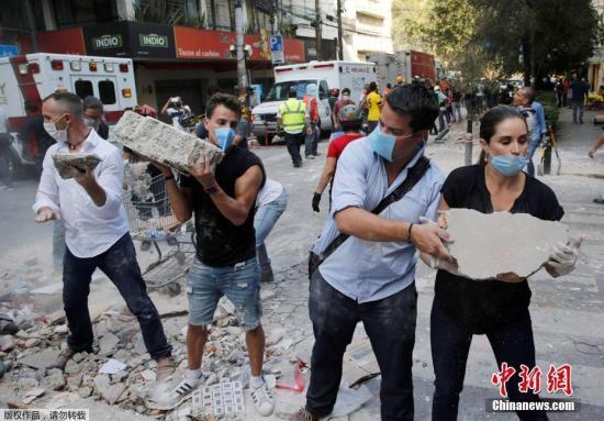 当地时间9月19日13时14分,墨西哥中部地区发生7.1级地震,截至目前已经导致超248人死亡,而且瓦砾下还有被掩埋者。民众恐慌逃至大街上,但也有很多人并没那么幸运。数分钟地震过后,市中心已是一片断垣残壁、烟尘满布景象。图为墨西哥城的一处倒塌的建筑废墟旁,志愿者徒手搬走石块,以方便救援行动展开。