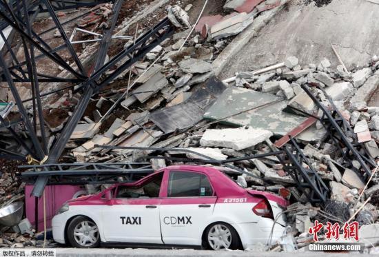图为墨西哥城一辆出租车被倒塌的建筑压扁。