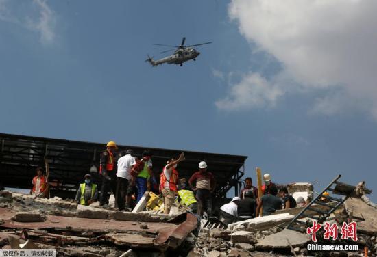 目前,墨西哥政府已出动军队参与救灾、维持灾区秩序。在墨西哥城,有志愿者和救援人员在废墟中寻找幸存者。在救援设备到位前,他们只能徒手刨出瓦砾碎石。图为一架军用直升机从建筑废墟上飞过。