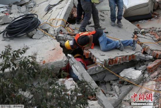 """在搜救现场,许多民众志愿加入有关单位协助移除瓦砾,有人手持着""""安静""""的标语,好让援救人员可听到生还者的声音。图为搜救人员正在开展救援行动。"""