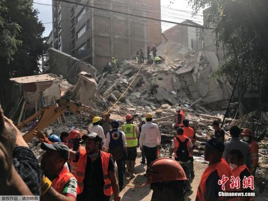 墨西哥总统培尼亚称地震造成墨西哥城内大量房屋倒塌。而就在32年前的今天,墨西哥1985年大地震造成7000多人死亡。图为墨西哥城的一处楼房废墟上,救援人员正在进行清理搜救工作。