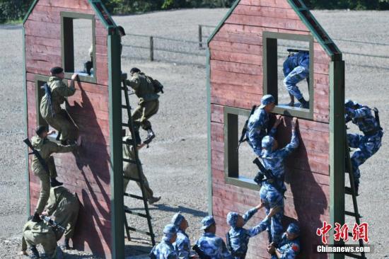 图为中俄双方海军陆战队员翻越障碍物。中新社记者 任东 摄