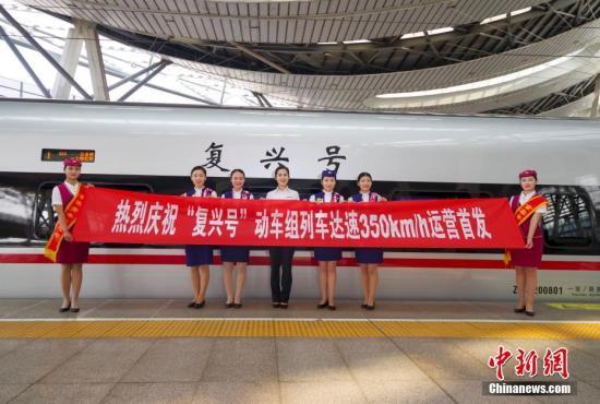 """9月21日,G13次""""复兴号""""列车乘务组在北京南站站台合影。当日,中国铁路调整运行图,京沪高铁线路上开行的""""复兴号""""动车组增加至7对,全部按最高时速350公里运行,京沪之间全程运行时间缩短至4小时30分左右。中国已成为世界上高铁商业运营速度最高的国家。中新社记者 贾天勇 摄"""