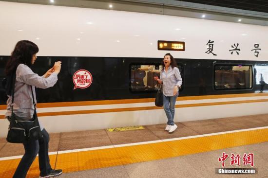 """资料图:旅客与""""复兴号""""列车合影留念。殷立勤 摄"""