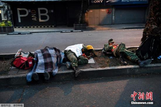 图为精疲力尽的救援士兵席地而睡。