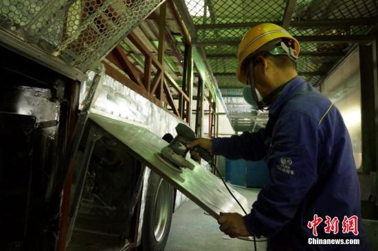 工人正在手工打磨车身钢板。 王昊阳 摄