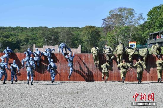 图为中俄双方海军陆战队员同时翻越障碍。中新社记者 任东 摄