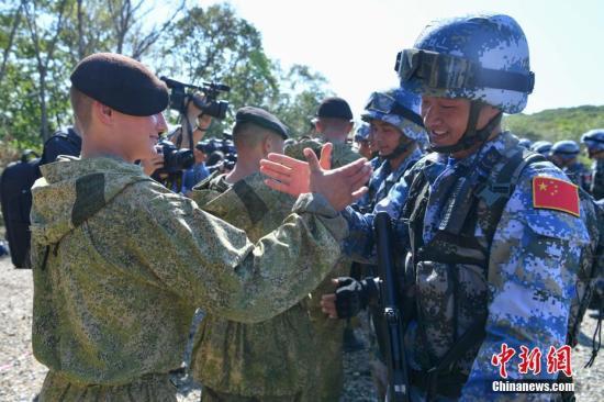 图为中俄双方海军陆战队员友好握手。 中新社记者 任东 摄