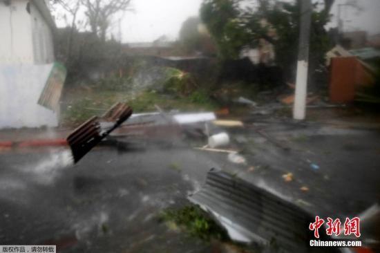 """在波多黎各瓜亚马,大风卷起建筑碎片四处扫荡,减弱为四级飓风的""""玛利亚""""破坏力依然巨大。"""