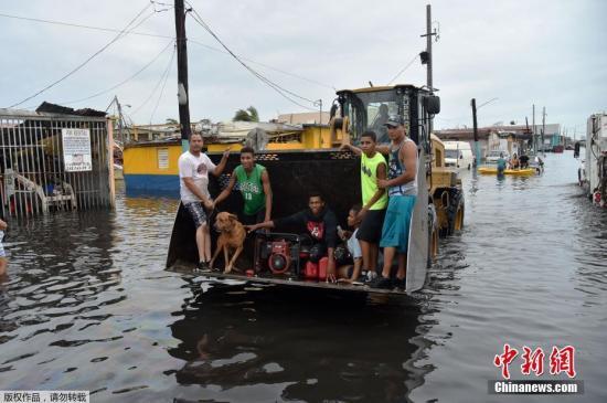 """当地时间2017年9月21日,波多黎各,当地遭飓风侵袭,房屋被毁,街道被淹。美国国家飓风中心发布消息称,飓风""""玛利亚""""当地时间20日袭击了美属波多黎各。图为波多黎各卡塔诺Juana Matos镇,当地民众乘坐挖掘机渡过积水的街道。"""