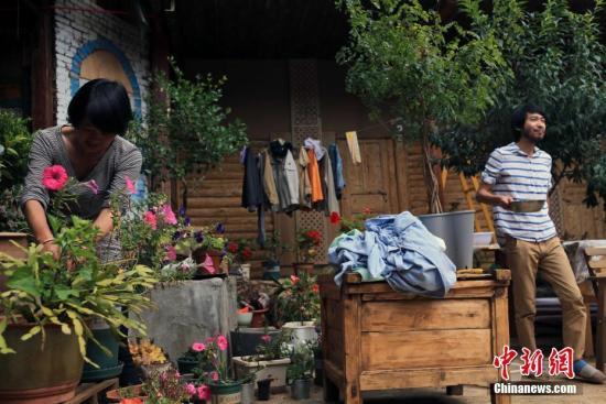 """9月21日,在四川省盐源县泸沽湖镇五支洛村的一座传统摩梭四合院里,35岁的朱文卿与自己的""""阿夏""""高佐直玛一起打水浇花。""""走婚""""习俗作为摩梭人的一种婚姻模式,一直被外界所热议。情投意合的男女确定关系后,男方会到女方家走婚,维持感情并生养儿女,男性称女方为""""阿夏"""",女性称男方为""""阿注""""。来自上海的朱文卿就是这样一位""""走""""入摩梭家庭的女婿。 中新社记者 王磊 摄"""
