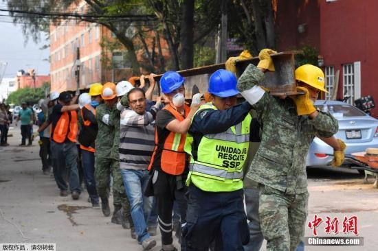 救援人员从震后废墟中救出了50多人,墨西哥总统培尼亚在全国讲话中称,眼下的当务之急是救人,坚信仍然可能从废墟中救出更多生还者。图为救援队员合力抬一根铁梁。