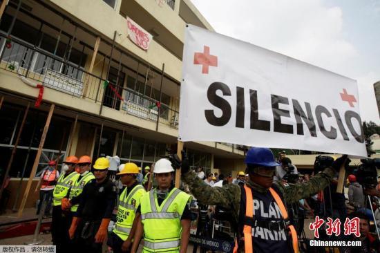 当地时间9月21日,墨西哥首都墨西哥城地震救援人员举起拳头示意保持安静,这样才能更好的听到废墟下的声音。