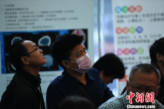 专家提醒,经常头晕、腹胀需警惕慢粒白血病。图为患者戴着口罩认真听医生的讲解。陈超 摄