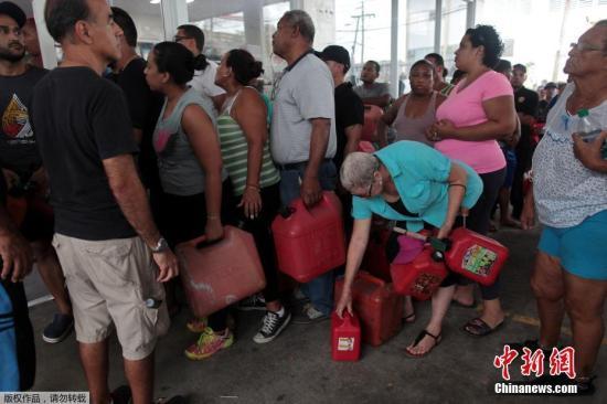 """资料图:当地时间2017年9月22日,飓风""""玛丽亚""""过境后,波多黎各民众在加油站排队购买汽油。"""