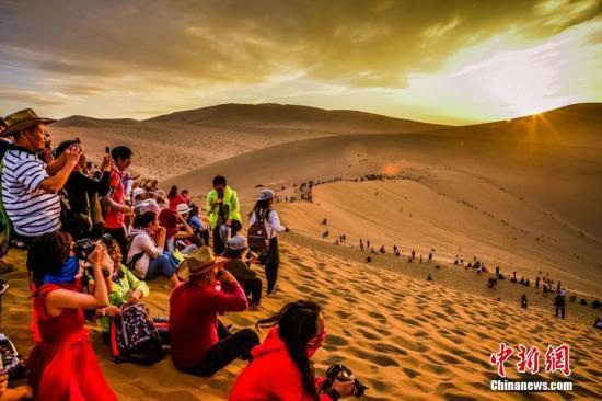 资料图:甘肃敦煌美丽的大漠风光吸引游客。王斌银 摄