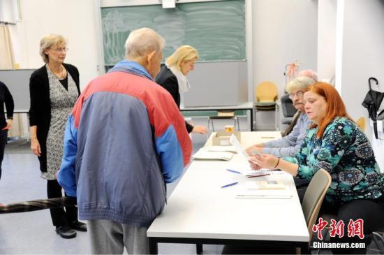 当地时间9月24日上午,德国第十九届联邦议院选举正式拉开帷幕。本届德国大选共有符合资格选民6150万人,其结果将决定下届总理人选和政府组成。图为当天上午8时在首都柏林的一处投票站内,工作人员查验前来投票选民的证件。 中新社记者 彭大伟 摄
