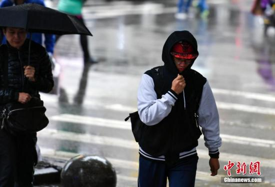 9月24日,新疆乌鲁木齐市降下秋雨,外出民众裹紧衣领快步前行。 中新社记者 刘新 摄