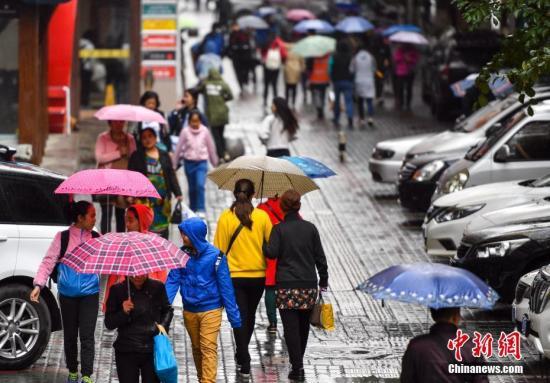资料图:新疆乌鲁木齐市降下秋雨,外出民众打着雨伞快步前行。 记者 刘新 摄