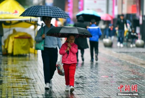 资料图:9月24日,新疆乌鲁木齐市降下秋雨,外出民众打着雨伞快步前行。 中新社记者 刘新 摄