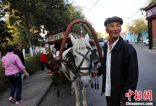 资料图:吐尔逊在新疆喀赞其民俗旅游区街上揽客,这将为他带来一笔不菲的收入。新疆维吾尔自治区旅游业2015年旅游总消费达1022亿元,首次过千亿。预计2020年全区旅游就业人数达到 250万人,其中旅游扶贫乡村旅游从业人数达到100万人,带动30万贫困人口脱贫。 记者 李国庆 摄
