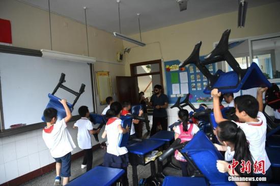 资料图:9月25日,重庆南岸区天台岗小学花园校区内举行反恐防暴演练。图为小学生们正在练习如何用身边工具来保护自己。中新社记者 陈超 摄