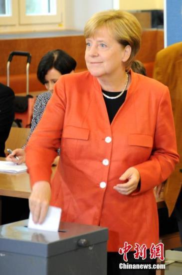 当地时间9月24日下午,德国总理默克尔在柏林洪堡大学的投票站参加大选投票。图为默克尔将选票放入投票箱。<a target='_blank' href='http://www.chinanews.com/'>中新社</a>记者 彭大伟 摄