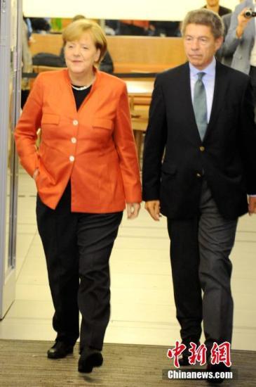 当地时间9月24日下午,德国总理默克尔在柏林洪堡大学的投票站参加大选投票。图为默克尔和丈夫绍尔步入投票站。中新社记者 彭大伟 摄