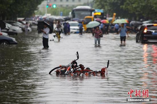 9月25日,南京城东银城东苑门口的道路上,市民在积水中涉水而行。持续的暴雨导致南京城不少路段严重积水,给市民的出行造成极大的影响。泱波 摄