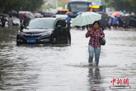 资料图:9月25日,南京城东银城东苑门口的道路上,市民在积水中涉水而行。泱波 摄