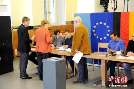 当地时间9月24日下午,德国总理默克尔在柏林洪堡大学的投票站参加大选投票。图为默克尔和丈夫绍尔在投票现场。中新社记者 彭大伟 摄