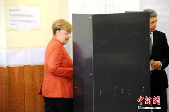 当地时间9月24日下午,德国总理默克尔在柏林洪堡大学的投票站参加大选投票。图为默克尔和丈夫绍尔在写票。中新社记者 彭大伟 摄