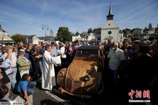 当地时间2017年9月23日,法国洛什,法国木工Michel Robillard用果木手工打造了一辆雪铁龙2CV汽车。图为牧师为这辆奇特的汽车祈福。
