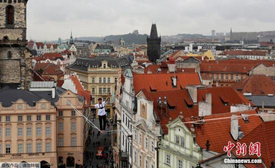 当地时间2017年9月25日,捷克布拉格,一名男子在老城广场上方挑战高空缆绳行走,为糖尿病人筹款。