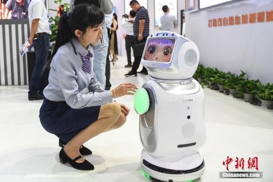 """资料图:工作人员展示""""人脸识别""""陪伴机器人性能。 中新社记者 张勇 摄"""