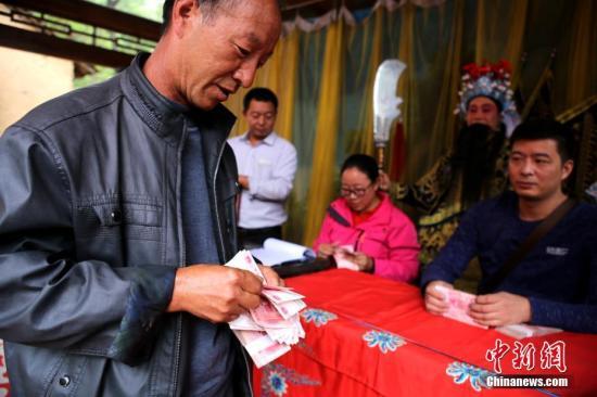 9月29日,国家级贫困县河南卢氏县新坪村,村民们兴高采烈的来到百草园广场参加首个股东分红大会。 王中举 摄
