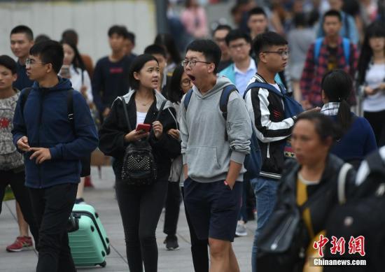 图为出行旅客在人群中打哈欠。中新社记者 陈超 摄