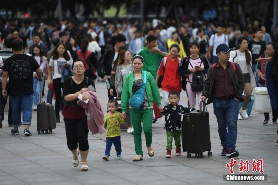 9月30日,重庆铁路迎来了国庆长假客流高峰。图为火车站广场上家长带着孩子踏上旅程。 中新社记者 陈超 摄